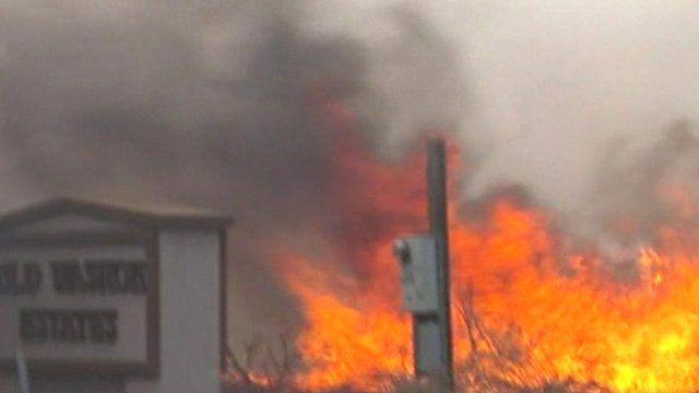 Flames surrounding utilities post and road sign