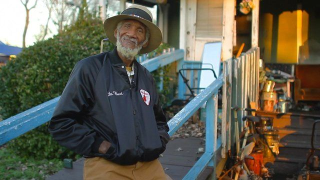 Bluesman Dr Burt stands in front of porch