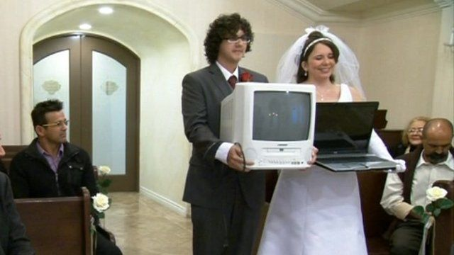 "Staged ""wedding"" between man carrying a TV and a woman carrying a laptop."