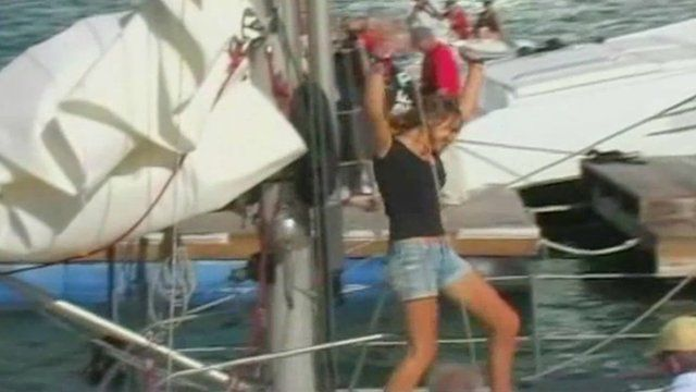 Laura Dekker raises her arms in the air triumphantly as she comes ashore.