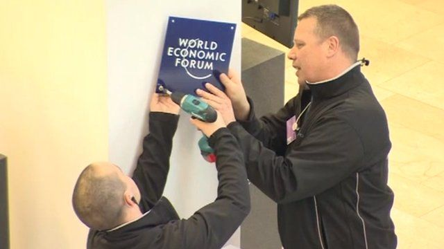 Workmen fixing a World Economic Forum sign to the wall