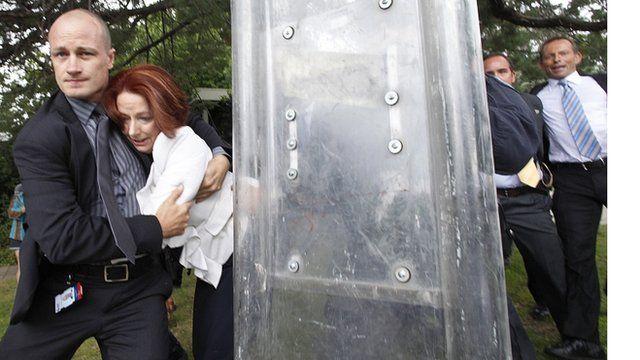 Australian PM is bundled away by a bodyguard