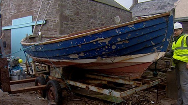 A fishing boat in dry dock on a trailer