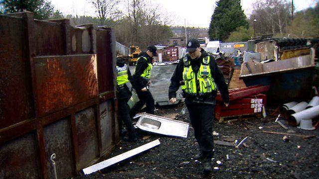 Police inspect a scrap metal dealer's yard