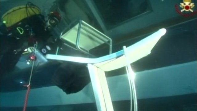 A white chair floating underwater in a submerged part of the Costa Concordia, with a masked diver in the background.