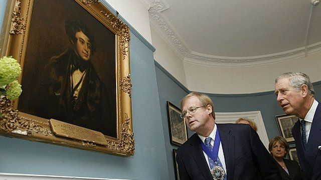 Prince Charles looks at portrait of Charles Dickens