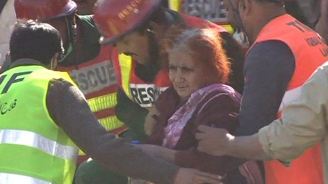 Rescue workers help a 65-year-old woman out of the rubble of the collapsed Lahore factory