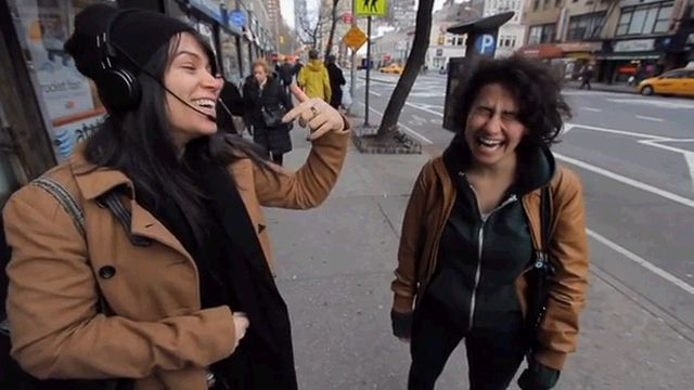 Two comedian standing and laughing on a sidewalk