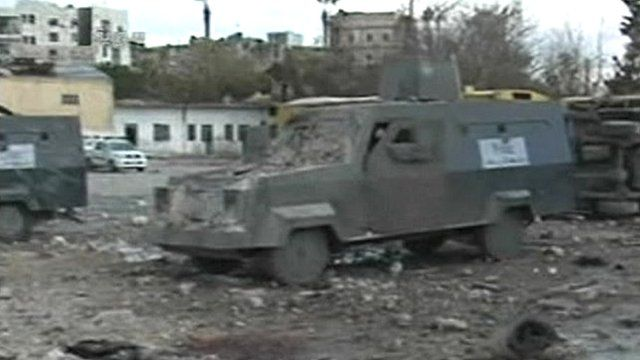Debris surrounds an armoured vehicle