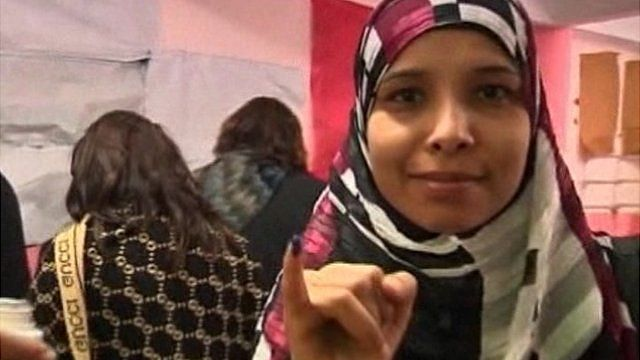 Egyptian woman showing the ink on her finger indicating casting her vote