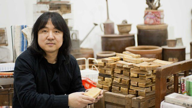 Song Dong holds a bar of soap, part of his Waste Not exhibition at The Curve (15 Feb- 12 June 2012). Photo by Jane Hobson, courtesy of Barbican Art Gallery