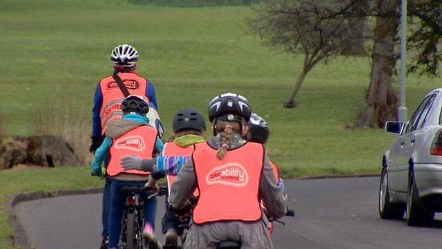 Adult cyclist leading 4 young cyclists on a road