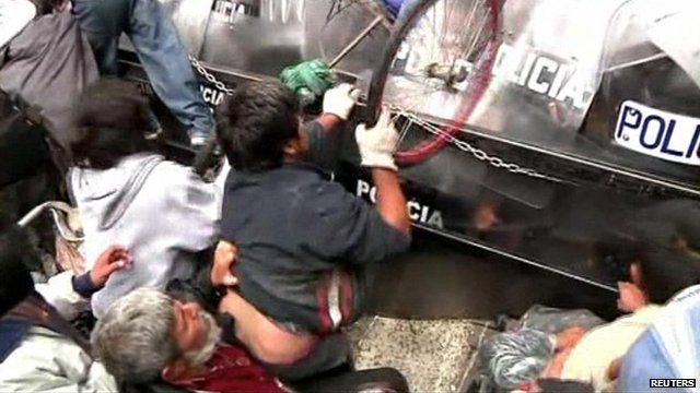 A protester uses a wheel from his wheelchair to hit police riot shields