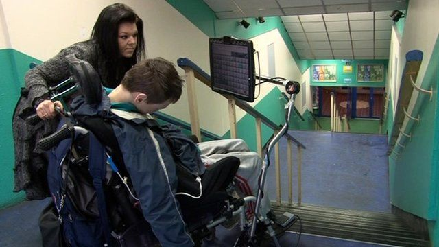 Nathan Popple in a wheelchair at the top of a staircase