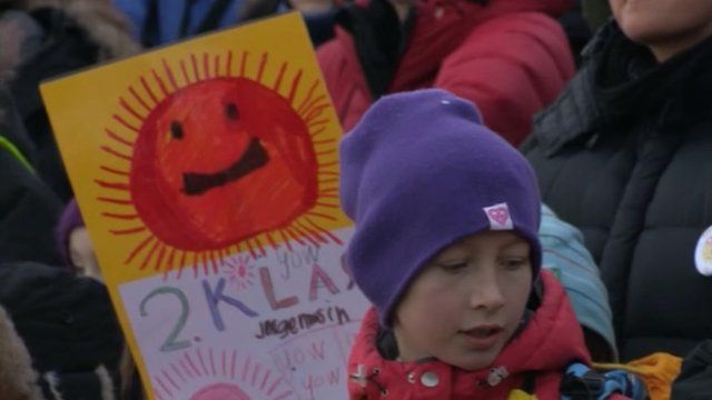 Child wearing woolly hat stands in front of child's poster showing the sun.