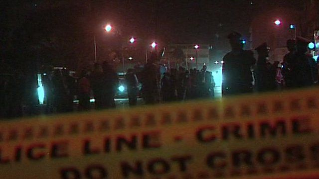 Police tape and officers at the scene of the grenade attack