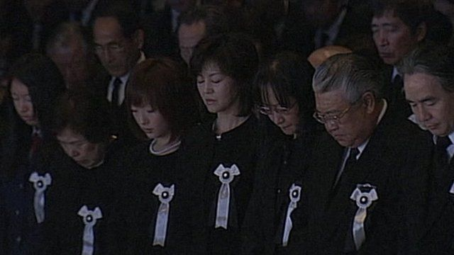 Heads bowed during the minute's silence on the anniversary of the earthquake in Japan