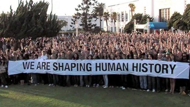 """Crowd holding banner saying """"We are shaping human history"""""""