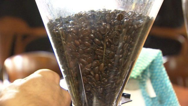 Coffee beans are funnelled in coffee shop grinder.
