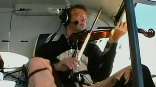A man plays a violin on board a helicopter.