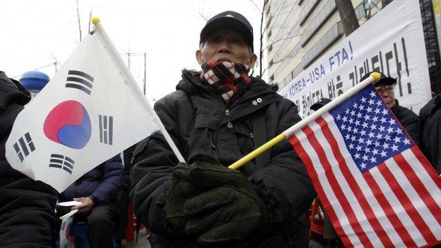 A South Korean activist celebrates the free trade agreement, in Seoul, South Korea.