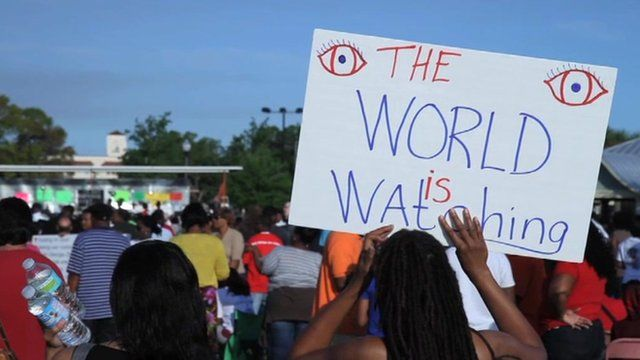 """Woman holds up sign which says """"The WORLD is watching""""."""