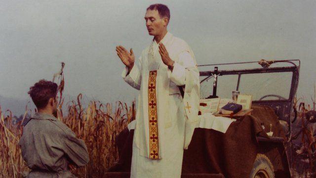Father Emil Kapaun prays over a soldier during the Korean War