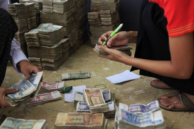 Workers count Burma's kyat banknotes at the office of a local bank