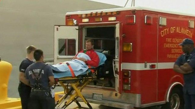 Injured yachtsman is carried into an ambulance by Coast Guard officials
