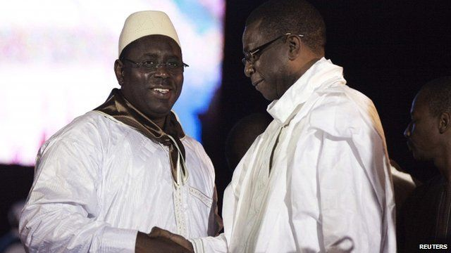 Senegalese presidential challenger Macky Sall (L) shakes hands with Grammy award-winning musician and political backer Youssou Ndour