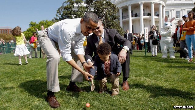 President Obama helps a boy to roll his egg