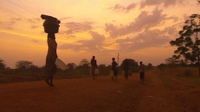 A woman carries a load above her head as the sun rises.