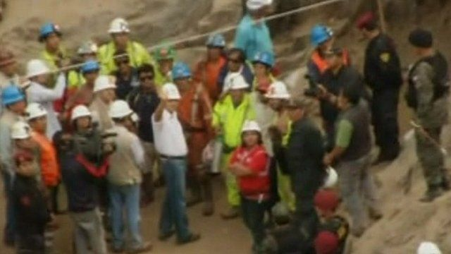 Rescuers wave outside the mine