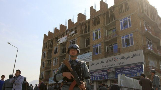Afghan policeman stand guard after a battle with Taliban insurgents who took over a building in Kabul