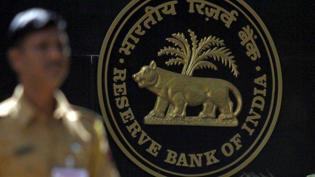 Policeman walks past logo of Reserve Bank of India in Mumbai.