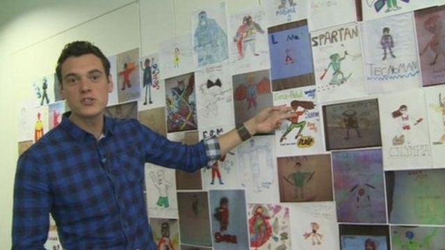 Joe beside a wall full of superhero drawings sent into Newsround