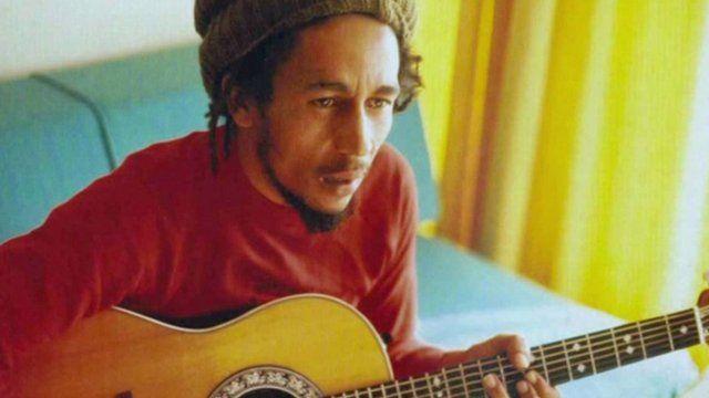 Bob Marley at home, playing guitar