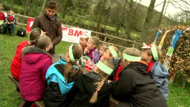 Ricky chatting to children at a countryside picnic table