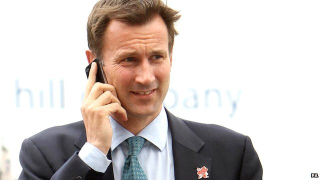 Culture Secretary Jeremy Hunt speaking on a mobile phone