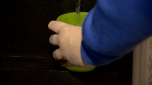 Teenager fills a cup of water