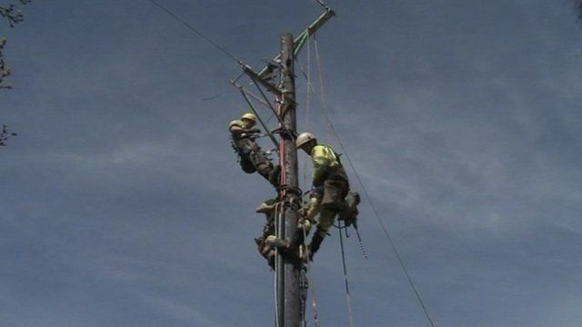 Engineers work on a wooden electricity pole