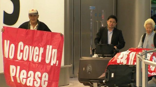 Relatives of one of the Malaysian men killed arrive with banners calling for an inquiry