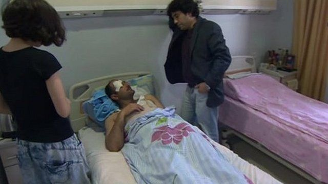 People visiting injured journalist in hospital bed