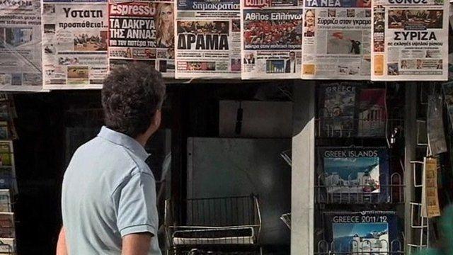 Man looks at Greek newspaper headlines