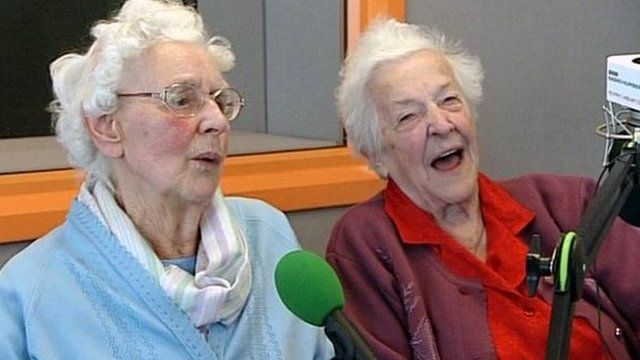 Beryl and Betty talking in front of the mic