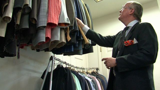 Man looks at a rack of clothing