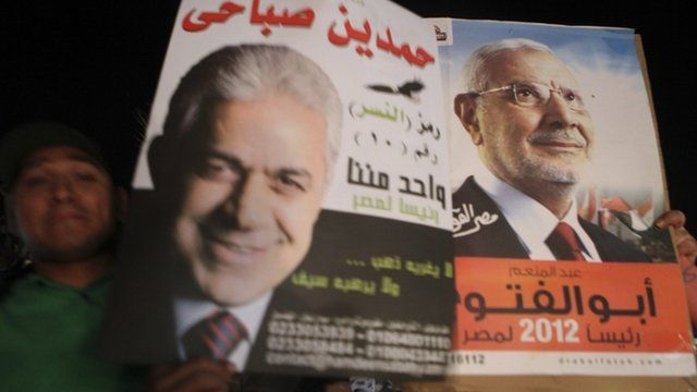A supporter of presidential candidate Sabahi holds his poster beside a supporter of presidential candidate El Fotouh