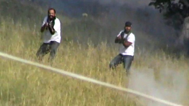 Two of the armed settlers aim at one Palestinian youth