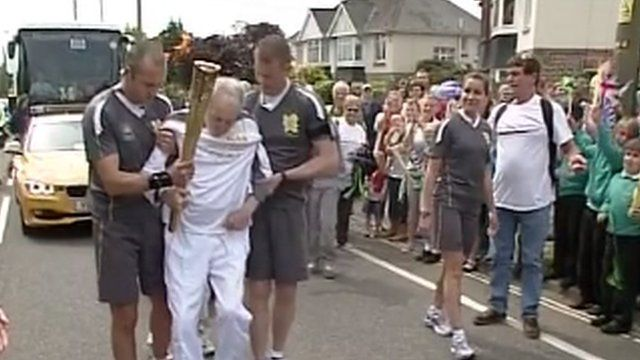 Andy Seward leaves his wheelchair to carry the Olympic flame