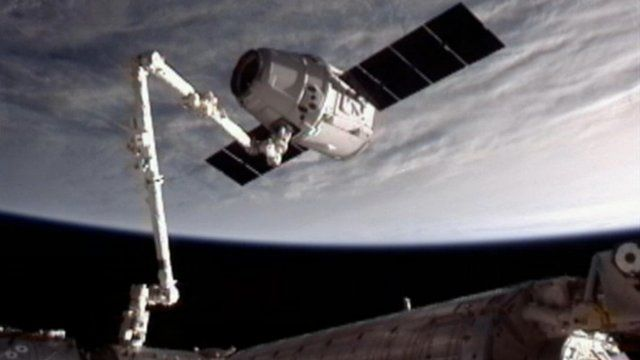 Dragon capsule at end of robotic arm